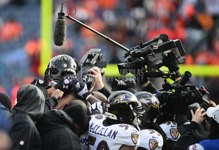 Jan 12, 2013; Denver, CO, USA; Baltimore Ravens players huddle as a television camera and microphone are held above against the Denver Broncos during the AFC divisional round playoff game at Sports Authority Field.  Mandatory Credit: Mark J. Rebilas-