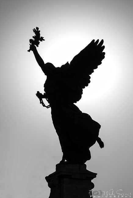 A silhouette of a statue on the Bridge of Angels in Rome, Italy.