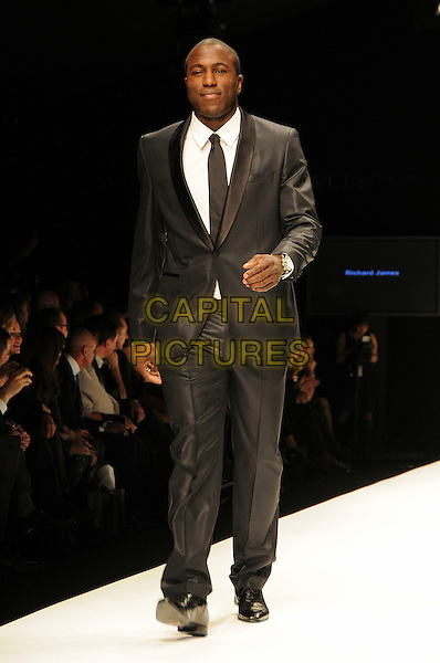 MODEL.The Fashion For Relief Haiti 2010 show for London Fashion Week Autumn/Winter 2010 at Somerset House, London, England..February 18th, 2010.LFW catwalk runway full length black suit.CAP/CAS.©Bob Cass/Capital Pictures.