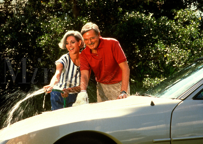 A smiling mature couple wash their car.