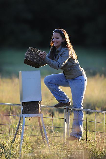 PURINA DEER BLOCK..Margo Kahla fills deer feeders with Quick Draw deer block. David Nelson helps out.