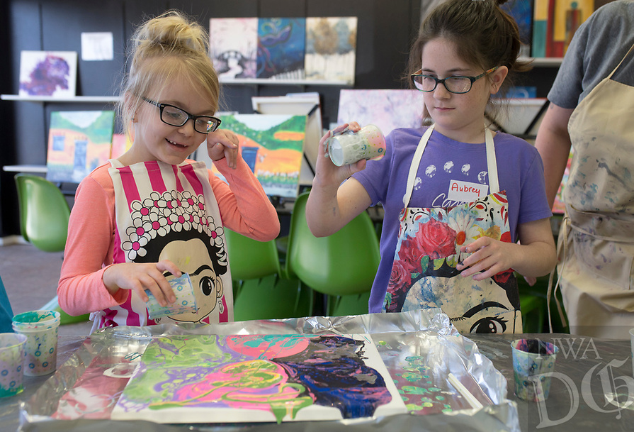 """NWA Democrat-Gazette/CHARLIE KAIJO Grace Cole, 7, of Fayetteville and Aubrey Moses, 11, of Bentonville (from left) paint during a Spring Break fluid art class, Monday, March 18, 2019 at iPaint in Rogers. <br /><br />Fluid art is any art where the paint moves and creates its own shapes said instructor Sue Mandel. The art uses silicone to create unique and unpredictable designs. """"No one piece will be the same,"""" she said."""