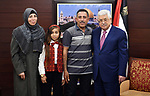 Palestinian President Mahmoud Abbas meets with Anam al-Attar, a Palestinian girl from Gaza with a kidney failure, at his headquarters in the West Bank city of Ramallah on March 2, 2018. Photo by Osama Falah