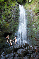 Female hikers stand on boulders at the base of Lulumahu Falls, Honolulu, O'ahu.