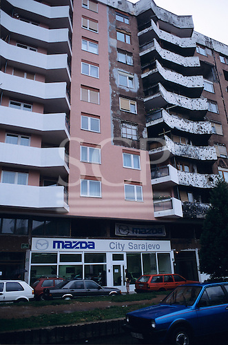 Sarajevo, Bosnia and Herzegovina. Multi - storey building partly reconstructed after the war.; Mazda saloon.