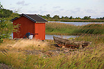 Old Weathered Wooden Boat on Shore by Fishing Shed on Kökar Island