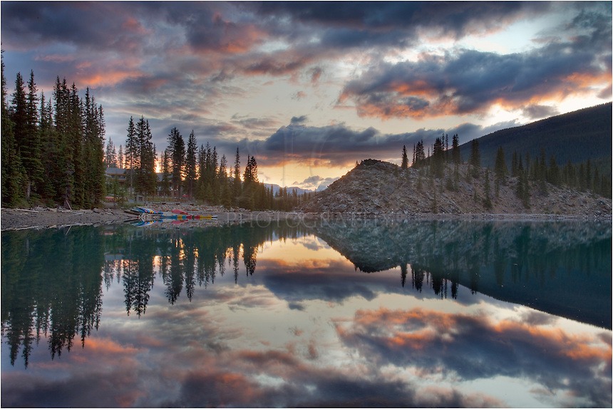 "At sunrise, the clouds begin to light up over Moraine Lake and the famous ""rock pile."" You can also see the colorful boats and kayaks that tourists use on beautiful summer days in the Canadian Rockies."