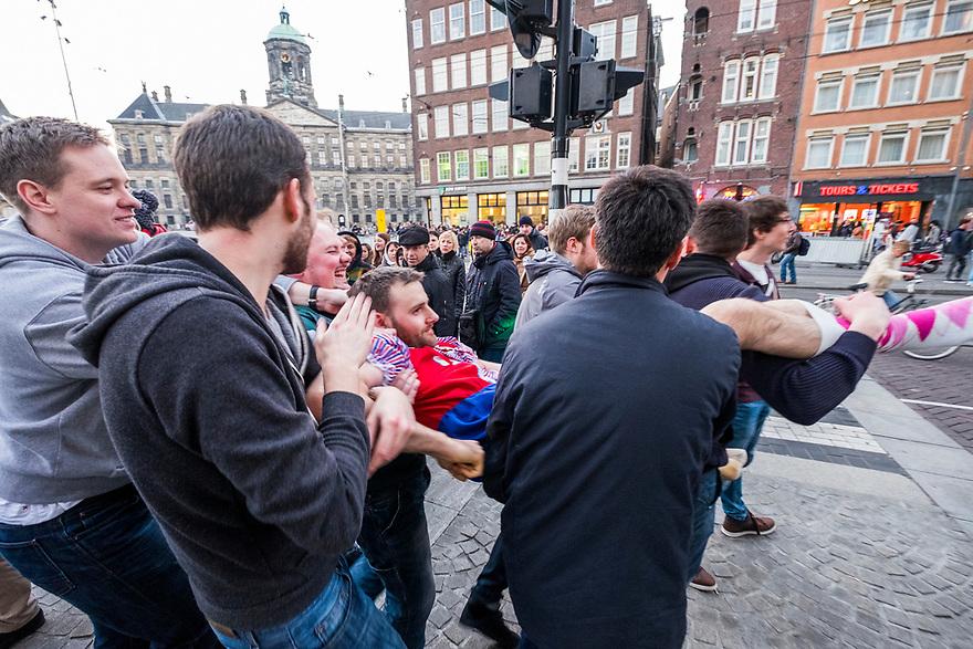 Nederland, Amsterdam, 20150313<br /> Bachelorparty, vrijgezellenfeest in centrum van Amsterdam. De aanstaande bruidegom wordt volledig dronken weggedragen van de dam.<br />  <br /> Foto: (c) Michiel Wijnbergh