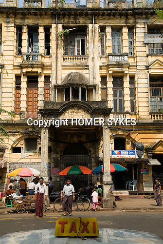 Merchant Street, once prosperous, these beautiful but now crumbling colonial building now house families in overcrowded damp, dark and insanitary conditions. A taxi waits for customers Merchant street, Yangon Myanmar ( Rangoon Burma ) South East Asia. 2006