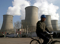 Morning commuters pass under the giant cooling towers of the Shengtou Power Plant in Shuozhou, Shanxi Province, China. The Shengtou plant is one of the country's largest coal burning power plant, taking readily available coal from the provinces many large mines. Tens of thousands of residents live extremely close to the plant..