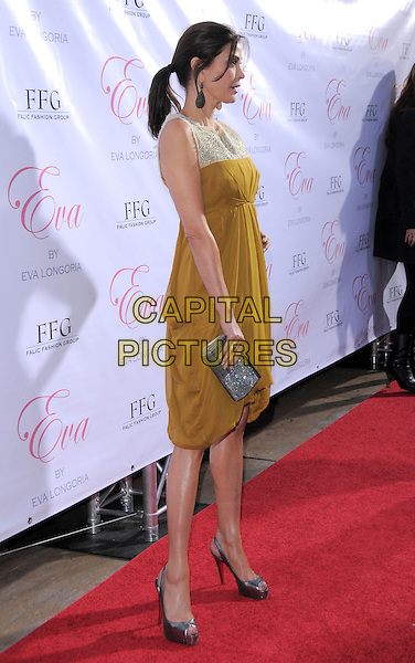 TERI HATCHER .The Eva by Eva Longoria Fragrance Launch held at Beso in Hollywood, California, USA. .April 27th, 2010.perfume full length green white yellow print pattern vintage sleeveless dress silver clutch bag  side profile ponytail shoes .CAP/RKE/DVS.©DVS/RockinExposures/Capital Pictures.