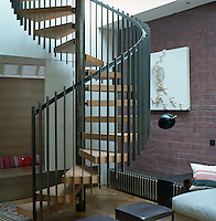 A contemporary spiral staircase with a simple wrought iron banister leads from the living room to the upper levels of the house