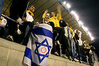 "Beitar Jerusalem soccer fans holding yellow and black flags and a national flag play drums during the match for the league against Bnei Sachnin in the Jerusalem stadium ""Tedy"". Bnei Sachnin is the only Arab club in the Israeli Prime League, as a result of that the Betar chants are specially racist during the games between the clubs...In the center of the Israeli flag a sticker proclaiming ""Kahane was right"", celebrating the notorious right-wing leader whose party was declared racist and outlawed by the Israeli state in 1985. Photo by Quique Kierszenbaum.."
