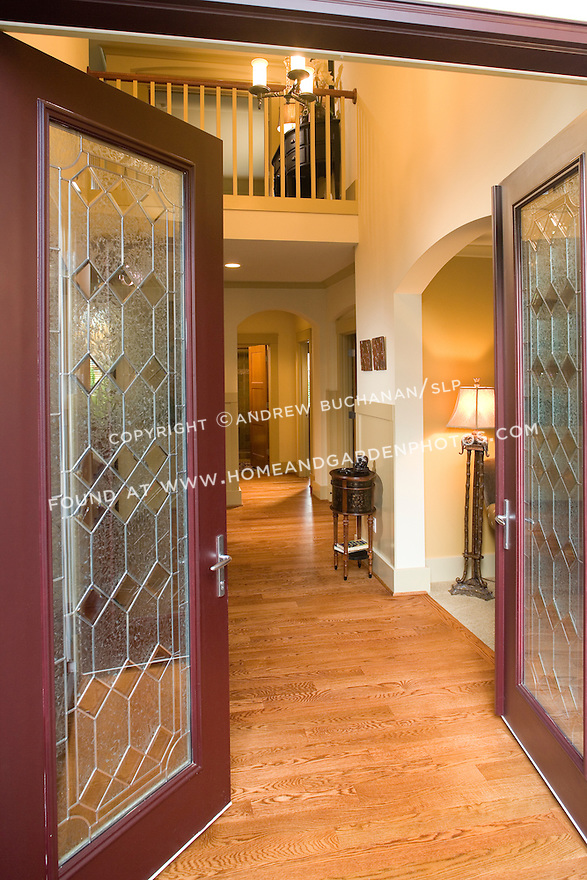 A deep red, double front door with leaded glass windows swings open into a dramatic two story 2-story front entry foyer featuring hardwood floors, arched doorways, and an upstairs balcony in this contemporary spec home.