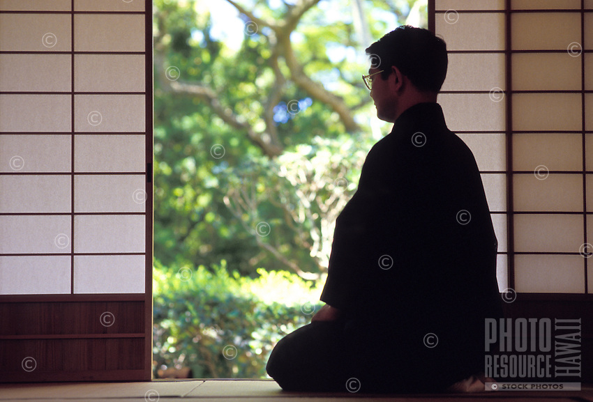 Monk sitting in quiet meditation near shoji doors