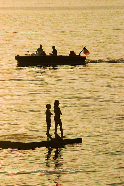 Silhouettes of a boat on a lake and children on a raft. Summer sunset.