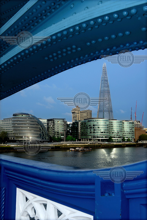 The Shard, Western Europe's tallest building (310 Metres) and City Hall (far left) and other Thameside buildings seen through part of the ornate iron work that forms part of Tower Bridge in London.