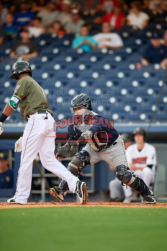 New Orleans Baby Cakes catcher Ramon Cabrera (38) reaches out to tag Nashville Sounds center fielder Kenny Wilson (11) after a dropped third strike during a game against the Nashville Sounds on April 30, 2017 at First Tennessee Park in Nashville, Tennessee.  The game was postponed due to inclement weather in the fourth inning.  (Mike Janes/Four Seam Images)