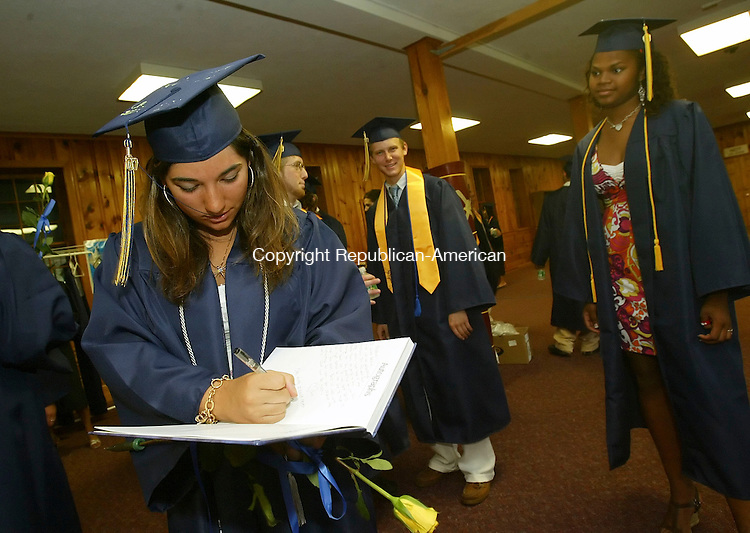 CHESHIRE, CT 6/02/07- 060207BZ06- Jessica Shoucair, of Kingston, Jamaica, signs a yearbook   before the start of commencement excercises at Cheshire Academy Saturday.<br /> Jamison C. Bazinet Republican-American