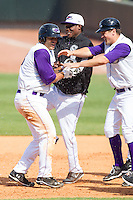 Grant Buckner (left) is doused with water by teammate Euclides Leyer (center) after driving in the winning run in the bottom of the 9th inning against the Frederick Keys at BB&T Ballpark on May 18, 2014 in Winston-Salem, North Carolina.  The Dash defeated the Keys 7-6.  (Brian Westerholt/Four Seam Images)