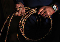 "Sonny Keakealani, one of the most respected cowboys in the community and patriarch of the Keakealani family, holds his favorite hand-braided rawhide rope. Sonny has mentored many younger cowboys over the years and while now offiially retired from Parker Ranch, still works a few days a week for a ranch and is often called on by old friends and ranch owners to help out with branding, weaning and moving cattle. ""We loved the lifestyle. Money didn't mean nothing.  We just enjoyed going out. Even if you got wet, you got scolded, that was part of our love, our life!"" says Keakealani reflecting back on his years working at Parker Ranch."
