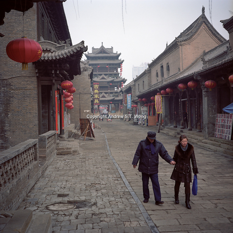 A Chinese woman helps her father as they walk through the old city area of Yuci in Jinzhong City in Shanxi province, 2012. (Mamiya 6, 75mm f3.5, Kodak Ektar 160 film)