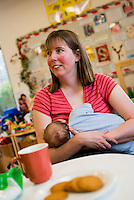 A mother breastfeeding her young baby at a breastfeeding drop-in support group.<br /> <br /> Image from the &quot;We Do It In Public&quot; documentary photography project collection: <br />  www.breastfeedinginpublic.co.uk<br /> <br /> Hampshire, England,UK<br /> 13/03/2013