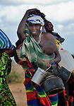 A newly arrived refugee mother carries her family's belongings through the Dadaab camp in northeastern Kenya. Already the world's world's largest refugee settlement, Dadaab has swelled in recent weeks with tens of thousands of recent arrivals fleeing drought in Somalia. The Lutheran World Federation, a member of the ACT Alliance, is manager of the camp, and in July opened a new extension to begin housing the newest refugees.