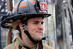A firefighter smiling at a fire scene
