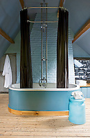 The brick walls of this attic bathroom have been painted azure blue with bath and telephone table to match