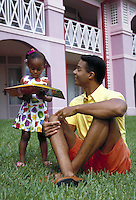 AFRICAN-AMERICAN FATHER LOOKING AT A PICTURE BOOK WITH HIS TODDLER DAUGHTER. FATHER AND TODDLER DAUGHTER. ORLANDO FLORIDA.