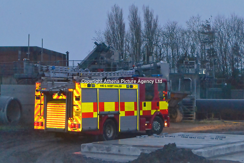 Pictured: Site workers with rescuers at the scene of the rescue operation at a construction site in Llanelli, Wales, UK. Tuesday 19 March 2019<br /> Re: A rescue operation took place after a worker got stuck in a 20ft hole on a construction site.<br /> The incident happened on New Dock Street, Llanelli, west Wales, after a skip of concrete fell as it was being lowered.<br /> Three workers were in the hole, with two able to climb out, but a third fell awkwardly and needed help.<br /> Two fire crews and a specialist line rescue team were sent to help the worker at about 5pm on Tuesday.