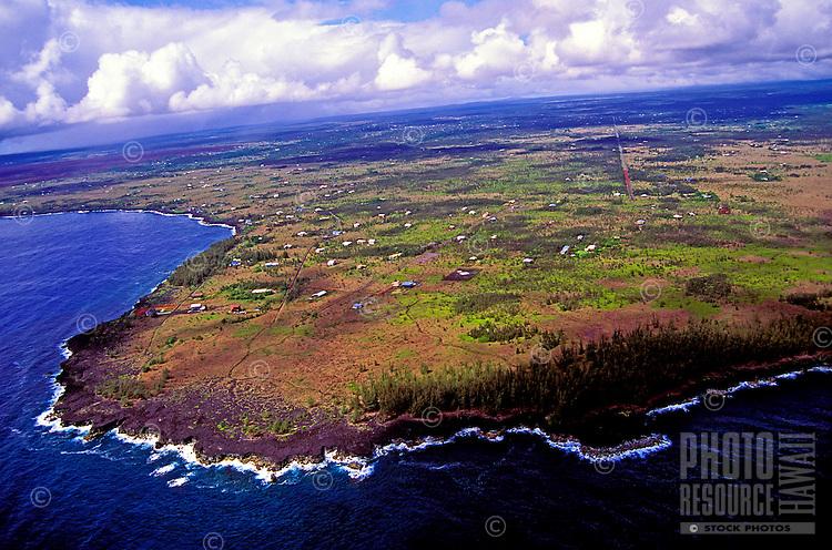 Homes sparsely dot the landscape on the black lava rock Puna coastline.