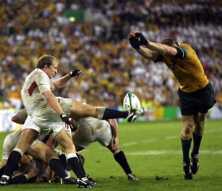 Photo: Richard Lane..Australia v England. Rugby World Cup Final, at the Telstra Stadium, Sydney. RWC 2003. 22/11/2003. .Matt Dawson kicks clear as Srirling Mortlock attempts a charge down.