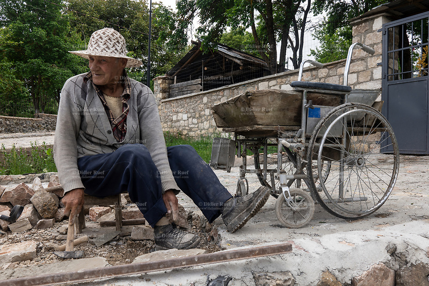 Albania. Voskopojë, An elderly disabled man is fixing the pavement stones at the entrance of his home.The cement is in a wooden basin placed on a wheelchair. Voskopojë is a village in Korçë County in southeastern Albania. 21.05.2018 © 2018 Didier Ruef