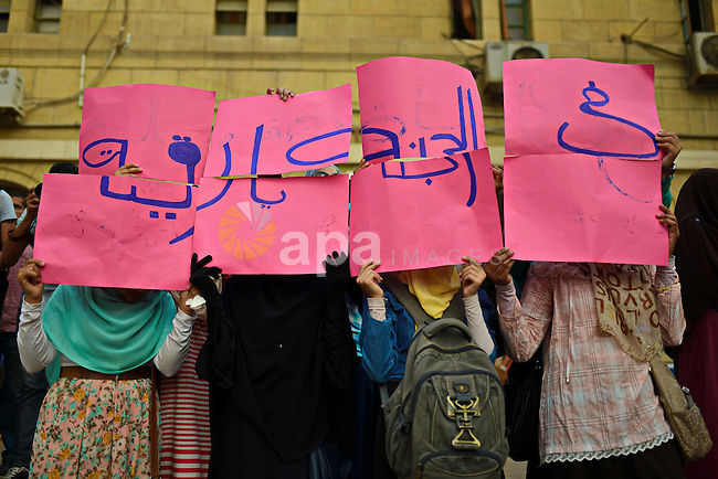 Egyptian students who support Muslim Brotherhood and ousted President Mohammed Morsi, hold placards during a demonstration demanding for release their fellow Radwa Jamal, who was arrested by Egyptian police, at Cairo University on November 5, 2014. Photo by Amr Sayed