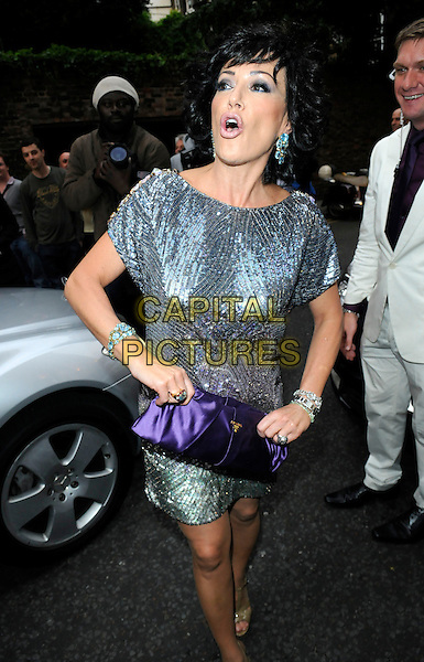 NANCY DELL'OLLIO.The WTA Tour Pre-Wimbledon Party,  Kensington Roof Gardens, London, England..June 18th, 2009.full length silver blue sequins sequined dress purple silk satin clutch bag dell olio mouth open funny face .CAP/FIN.©Steve Finn/Capital Pictures.