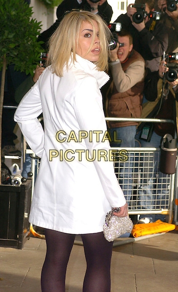 BILLIE PIPER.The South Bank Show Awards,.London, England, 27th January 2006..half length  short white coat belted mac black tights  silver purse clutch bag back looking over shoulder.Ref: CAN.www.capitalpictures.com.sales@capitalpictures.com.©Capital Pictures
