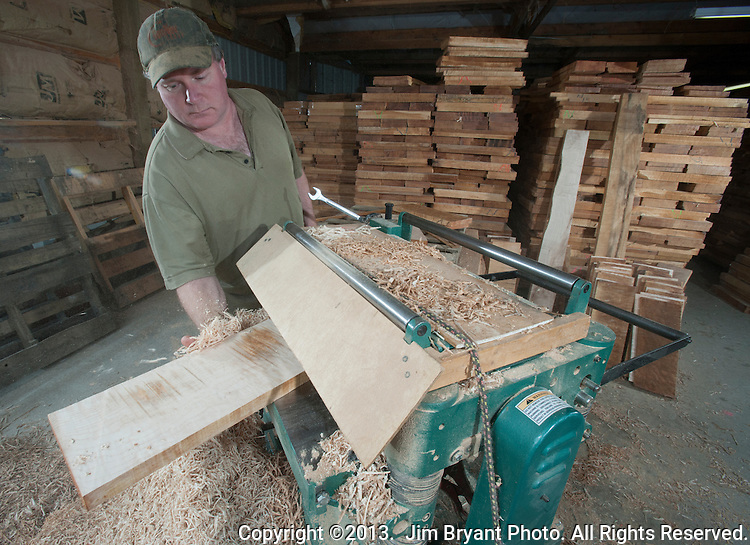Don Van Orman, guitar maker extraordinaire uses a plane to smooth maple wood plank. Van Orman is a major buyer of Maple. He operates on a 40-acre spread in Elma, Washington. He makes over 25 custom made guitars a year.  ©2013.  Jim Bryant Photo. All Rights Reserved.