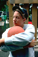 17 year old high school student thoughtfully hugging basketball.  St Paul Minnesota USA