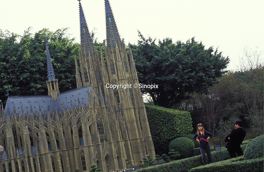 Chinese tourists taking photos besides the model of Cologne Cathedral at Windows of the World amusement park in Shenzhen, China. The amusement park has copied many of the worlds most famous monuments and attractions, mostly in minature and attracts millions of tourists annually.