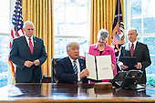 U.S. President Donald J. Trump (C-L) displays one of three executive actions that he said are 'designed to restore safety in America' while Vice President Mike Pence (L), Attorney General Jeff Sessions (R) and his wife, Mary Blackshear Sessions (C-R) look on in the Oval Office of the White House in Washington, DC, USA, 09 February 2017. On 08 February, after a contentious battle on party lines, the Senate voted to confirm Sessions as attorney general.<br /> Credit: Jim LoScalzo / Pool via CNP