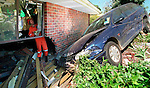 A State Emergency Service worker inspects damage to a house in that was hit by a car. Neither the driver of the car or occupants of the house were injured.