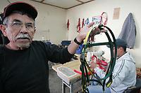 Adalberto Miranda Martinez muestra una Cabezada para caballos de carreras  en un area de costura don de ademas fabrican las pecharas.<br />.<br />Carlos Fimbres  al fondo en la maquina de cocer.