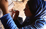 Petra, Jordan. A young Bedouin woman is putting traditional makeup on a tourist. Petra is the most visited tourist attraction in Jordan, a symbol of the country for its historical and archaeological importance. It has been a UNESCO World Heritage Site since 1985. The Bedouin families that have been living for centuries in the caves of Petra, agreed to move out into a small village, built near the site of Petra. Most of them earn their living from tourism which seems to be the only option available, especially for the younger generations.