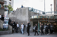 August 25, 2018: Pedestrians react as supporters of the neo Nazi Nordic Resistance Movement NRM (Nordiska motståndsrörelsen) are escorted by police forces (not pictured) out of a metro station after a demonstration at the Kungsholmstorg square in Stockholm, Sweden. An estimate of 200 supporters of the neo-Nazi organisation held a six-hour rally guarded by a strong police deployment.