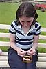 Homeless teenage girl sitting on park bench rolling cigarette,
