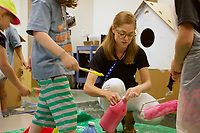 NWA Democrat-Gazette / ELIZABETH GREEN Cami Hedstrom, a senior at the University of Arkansas at Fort Smith and an intern for the Amazeum, helps children with paint Wednesday, June 26, 2019 during one of the museum's summer camps.