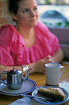 "Woman sitting in cafe with tea and desert on table along the ""Ave"" University District Seattle Washington State USA   MR"