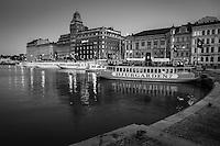 Skärgårdsbåtar vid kajen vid Nybroviken på natten i Stockholm i svartvitt.